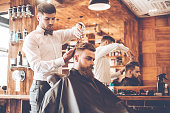Side view of young bearded man getting haircut by hairdresser while sitting in chair at barbershop