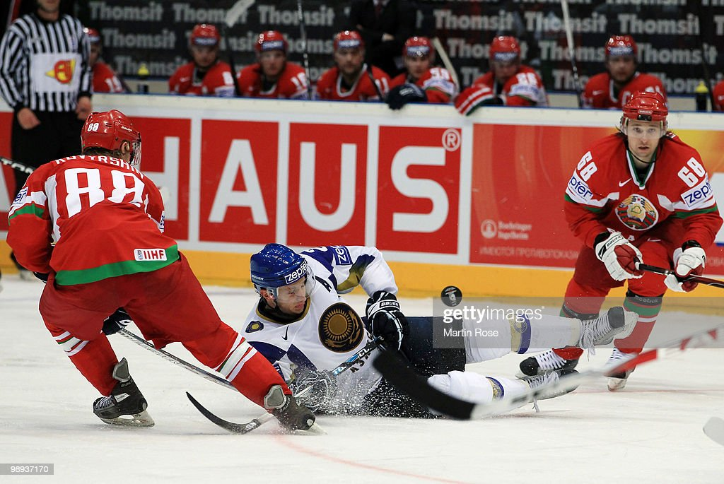 Evgeni Kovyrshin (L) of Belarus and Dmitri Dudarev (R) of Kazakhstan battle for the puck during the IIHF World Championship group A match between Slovakia and Russia at Lanxess Arena on May 9, 2010 in Cologne, Germany.