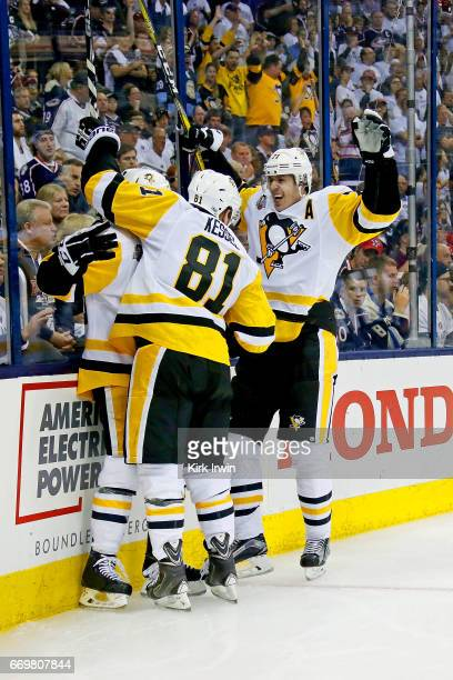 Evgeni Malkin and Phil Kessel congratulate Jake Guentzel all of the Pittsburgh Penguins after scoring a goal during Game Three of the Eastern...