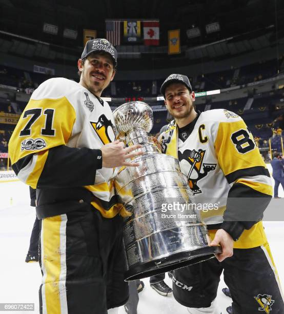 Evgeni Malkin and Sidney Crosby of the Pittsburgh Penguins celebrate with the Stanley Cup following a victory over the Nashville Predators in Game...