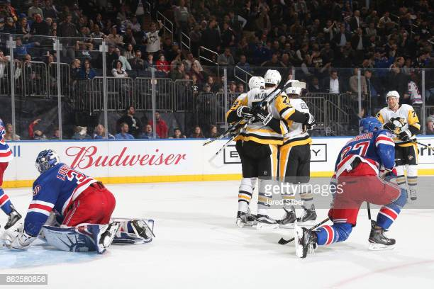 Evgeni Malkin of Pittsburgh Penguins celebrates with teammates after the overtime winning goal against Henrik Lundqvist of the New York Rangers at...