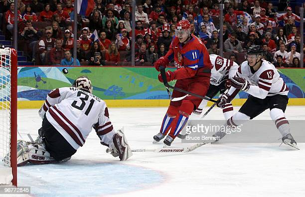 Evgeni Malkin of Russia has his shot on goal saved by Edgars Masalskis of Latvia during the ice hockey men's preliminary game between Russia and...