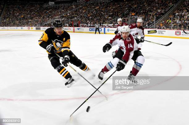 Evgeni Malkin of the Pittsburgh Penguins and Blake Comeau of the Colorado Avalanche battle for a puck at PPG Paints Arena on December 11 2017 in...