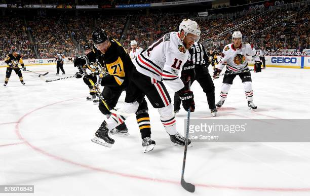 Evgeni Malkin of the Pittsburgh Penguins and Cody Franson of the Chicago Blackhawks battle for the puck at PPG Paints Arena on November 18 2017 in...