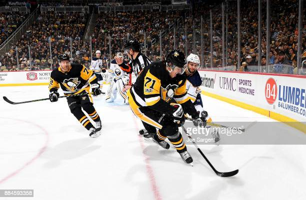 Evgeni Malkin of the Pittsburgh Penguins and Marco Scandella of the Buffalo Sabres battle for a puck at PPG Paints Arena on December 2 2017 in...