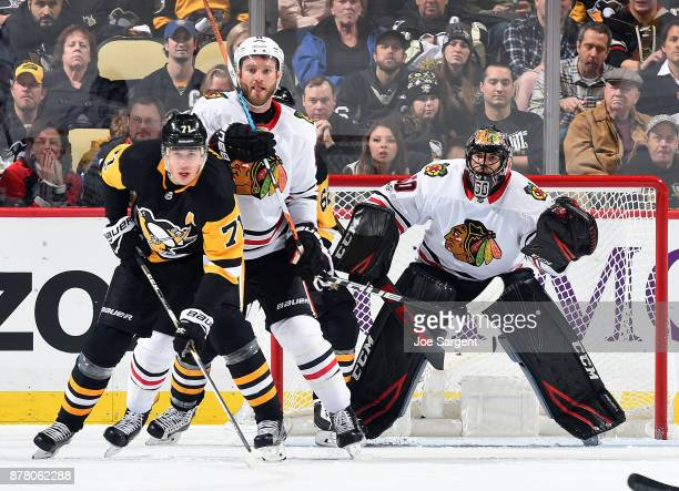 Evgeni Malkin of the Pittsburgh Penguins battles for position against Cody Franson of the Chicago Blackhawks in front of Corey Crawford at PPG Paints...