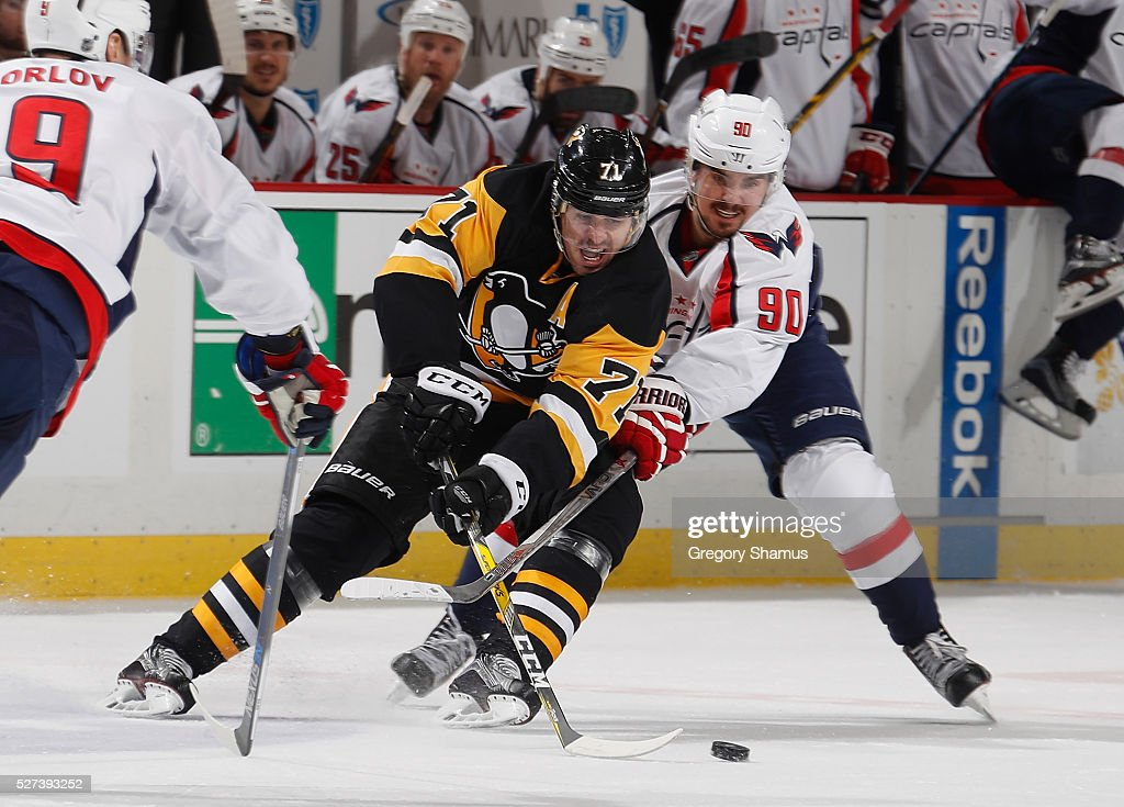 Evgeni Malkin of the Pittsburgh Penguins battles for the loose puck against Marcus Johansson of the Washington Capitals in Game Three of the Eastern...