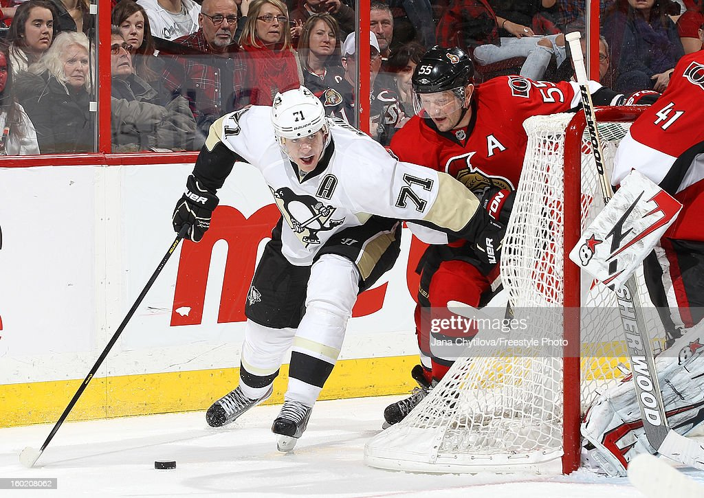 Evgeni Malkin #71 of the Pittsburgh Penguins carries the puck while being chased by Sergei Gonchar #55 of the Ottawa Senators during an NHL game at Scotiabank Place on January 27, 2013 in Ottawa, Ontario, Canada.