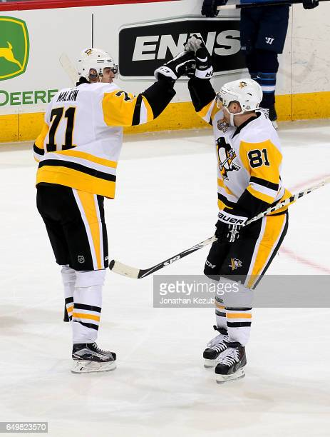 Evgeni Malkin of the Pittsburgh Penguins celebrates his first period goal against the Winnipeg Jets with teammate Phil Kessel at the MTS Centre on...