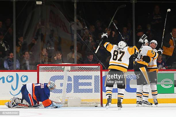 Evgeni Malkin of the Pittsburgh Penguins celebrates his third period goal with teammates Sidney Crosby and Brian Dumoulin at the Barclays Center on...