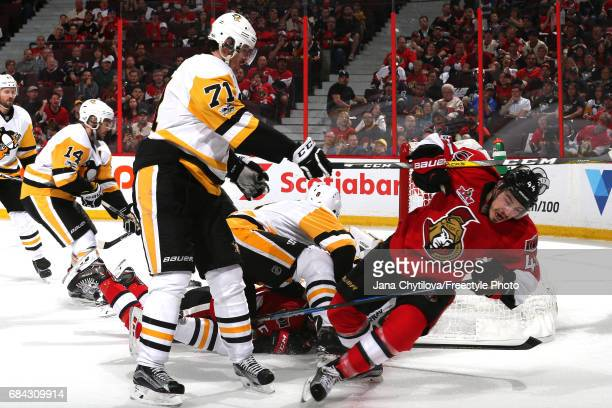 Evgeni Malkin of the Pittsburgh Penguins checks JeanGabriel Pageau of the Ottawa Senators to the ice during the second period in Game Three of the...
