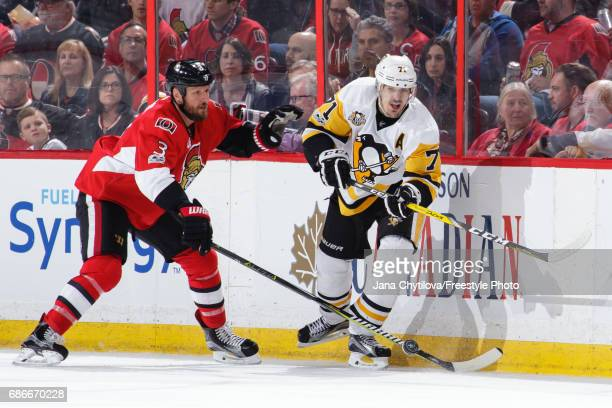 Evgeni Malkin of the Pittsburgh Penguins chips the puck past Marc Methot of the Ottawa Senators in Game Four of the Eastern Conference Final during...