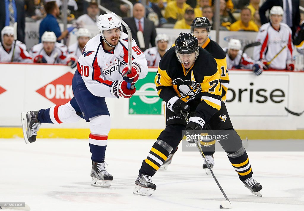 Evgeni Malkin of the Pittsburgh Penguins handles the puck against Marcus Johansson of the Washington Capitals in Game Three of the Eastern Conference...