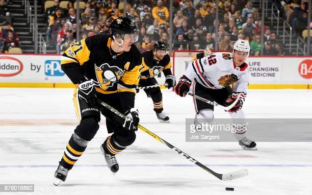 Evgeni Malkin of the Pittsburgh Penguins handles the puck against Gustav Forsling of the Chicago Blackhawks at PPG Paints Arena on November 18 2017...