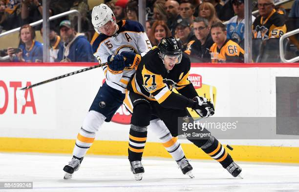 Evgeni Malkin of the Pittsburgh Penguins handles the puck against Jack Eichel of the Buffalo Sabres at PPG Paints Arena on December 2 2017 in...
