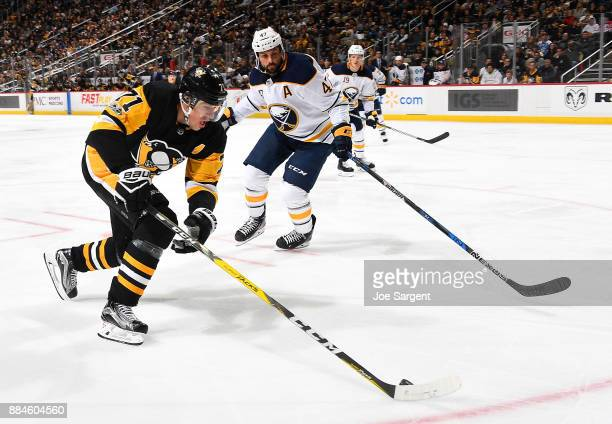 Evgeni Malkin of the Pittsburgh Penguins handles the puck against Zach Bogosian of the Buffalo Sabres at PPG Paints Arena on December 2 2017 in...