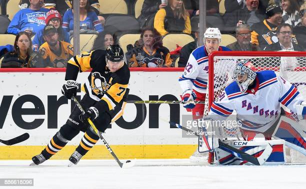 Evgeni Malkin of the Pittsburgh Penguins handles the puck against Ondrej Pavelec of the New York Rangers at PPG Paints Arena on December 5 2017 in...