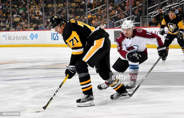 Evgeni Malkin of the Pittsburgh Penguins handles the puck against Blake Comeau of the Colorado Avalanche at PPG Paints Arena on December 11 2017 in...