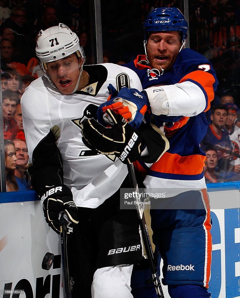 Evgeni Malkin #71 of the Pittsburgh Penguins is checked by Matt Carkner #7 of the New York Islanders during the third period in Game Six of the Eastern Conference Quarterfinals during the 2013 NHL Stanley Cup Playoffs at Nassau Veterans Memorial Coliseum on May 11, 2013 in Uniondale, New York.