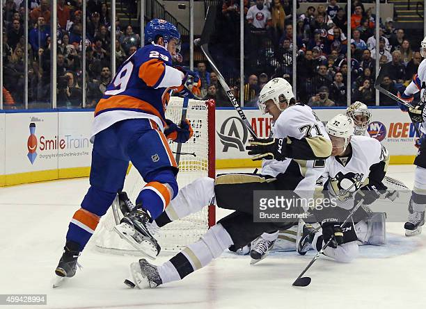 Evgeni Malkin of the Pittsburgh Penguins is hit by Brock Nelson of the New York Islanders during the second period at the Nassau Veterans Memorial...
