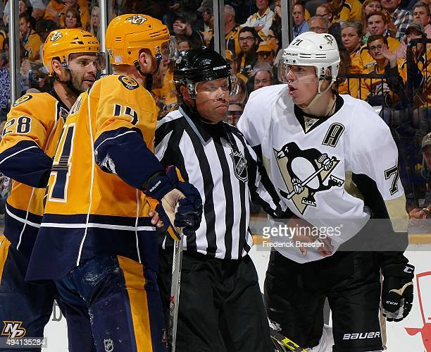 Evgeni Malkin of the Pittsburgh Penguins is seperated from Mattias Ekholm of the Nashville Predators by an official during the second period at...