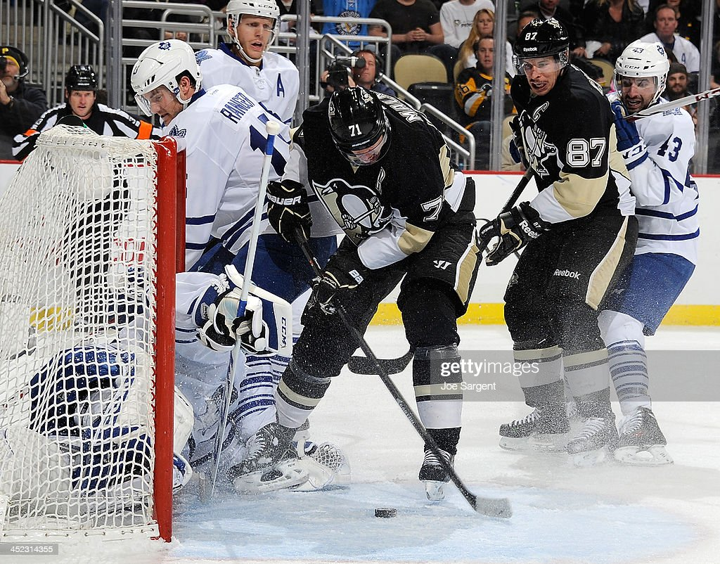 <a gi-track='captionPersonalityLinkClicked' href=/galleries/search?phrase=Evgeni+Malkin&family=editorial&specificpeople=221676 ng-click='$event.stopPropagation()'>Evgeni Malkin</a> #71 of the Pittsburgh Penguins knocks the loose puck in for a goal in front of <a gi-track='captionPersonalityLinkClicked' href=/galleries/search?phrase=Jonathan+Bernier&family=editorial&specificpeople=540491 ng-click='$event.stopPropagation()'>Jonathan Bernier</a> #45 and <a gi-track='captionPersonalityLinkClicked' href=/galleries/search?phrase=Paul+Ranger&family=editorial&specificpeople=544991 ng-click='$event.stopPropagation()'>Paul Ranger</a> #15 of the Toronto Maple Leafs on November 27, 2013 at Consol Energy Center in Pittsburgh, Pennsylvania. Pittsburgh won the game 6-5 in a shootout.