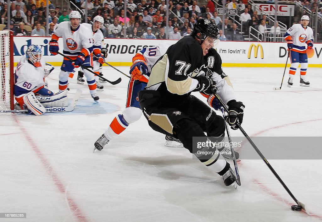 Evgeni Malkin #71 of the Pittsburgh Penguins moves the puck in front of Keith Aucoin #10 of the New York Islanders in Game One of the Eastern Conference Quarterfinals during the 2013 NHL Stanley Cup Playoffs at Consol Energy Center on May 1, 2013 in Pittsburgh, Pennsylvania.