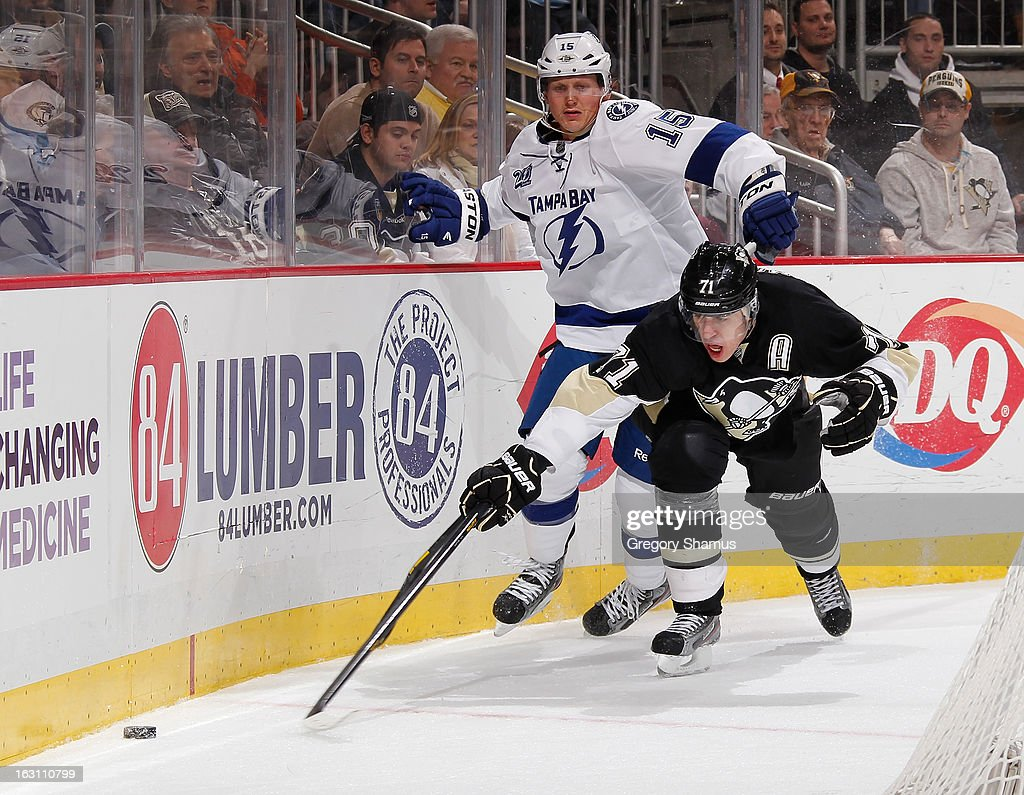 Evgeni Malkin #71 of the Pittsburgh Penguins reaches for the loose puck in front of Brian Lee #15 of the Tampa Bay Lightning on March 4, 2013 at Consol Energy Center in Pittsburgh, Pennsylvania.