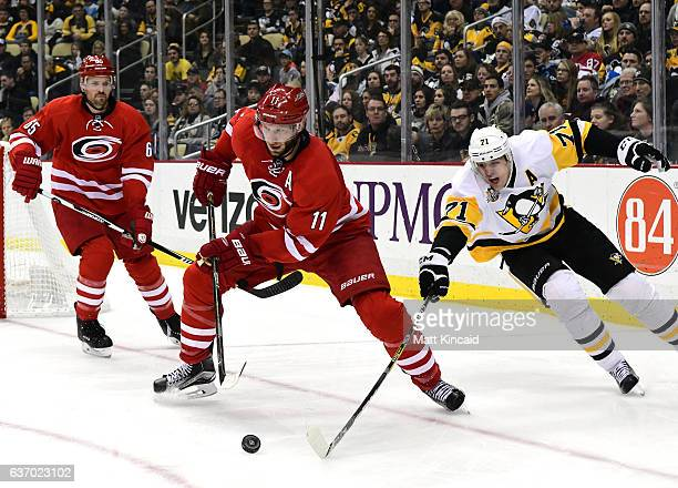 Evgeni Malkin of the Pittsburgh Penguins reaches for the puck against Jordan Staal of the Carolina Hurricanes at PPG PAINTS Arena on December 28 2016...