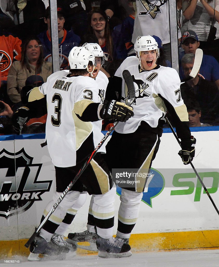 <a gi-track='captionPersonalityLinkClicked' href=/galleries/search?phrase=Evgeni+Malkin&family=editorial&specificpeople=221676 ng-click='$event.stopPropagation()'>Evgeni Malkin</a> #71 (R) of the Pittsburgh Penguins scores at 7:17 of the second period against the New York Islanders and is joined by Douglas Murray #3 (L) and <a gi-track='captionPersonalityLinkClicked' href=/galleries/search?phrase=James+Neal&family=editorial&specificpeople=1487991 ng-click='$event.stopPropagation()'>James Neal</a> #18 (C) in Game Four of the Eastern Conference Quarterfinals during the 2013 NHL Stanley Cup Playoffs at the Nassau Veterans Memorial Coliseum on May 7, 2013 in Uniondale, New York.