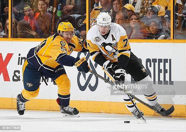 Evgeni Malkin of the Pittsburgh Penguins skates against Roman Josi of the Nashville Predators during an NHL game at Bridgestone Arena on October 22...