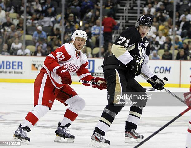 Evgeni Malkin of the Pittsburgh Penguins skates against Ryan Johnson of the Detroit Red Wings during a preseason game at Consol Energy Center on...