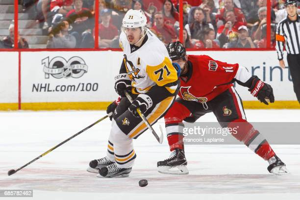 Evgeni Malkin of the Pittsburgh Penguins skates with the puck against Clarke MacArthur of the Ottawa Senators in Game Three of the Eastern Conference...