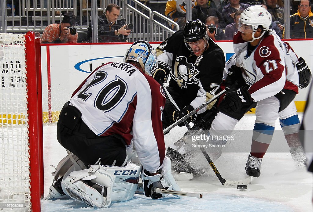 Evgeni Malkin of the Pittsburgh Penguins takes a shot in front of Reto Berra and Andreas Martinsen of the Colorado Avalanche at Consol Energy Center...