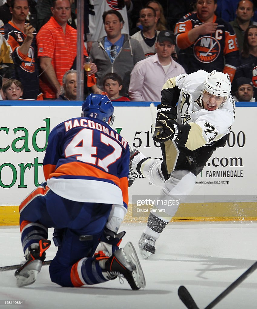 <a gi-track='captionPersonalityLinkClicked' href=/galleries/search?phrase=Evgeni+Malkin&family=editorial&specificpeople=221676 ng-click='$event.stopPropagation()'>Evgeni Malkin</a> #71 of the Pittsburgh Penguins takes the shot against Andrew MacDonald #47 of the New York Islanders in Game Three of the Eastern Conference Quarterfinals during the 2013 NHL Stanley Cup Playoffs at the Nassau Veterans Memorial Coliseum on May 5, 2013 in Uniondale, New York. The Penguins defeated the Islanders 5-4 in overtime.