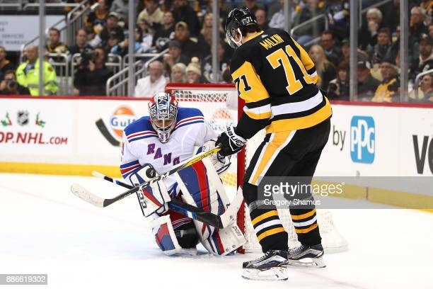 Evgeni Malkin of the Pittsburgh Penguins tries to deflect in a shot past Ondrej Pavelec of the New York Rangers during the second period at PPG...