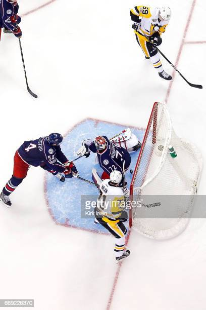 Evgeni Malkin of the Pittsburgh Penguins watches as teammate Jake Guentzel beats Sergei Bobrovsky of the Columbus Blue Jackets for a goal during the...