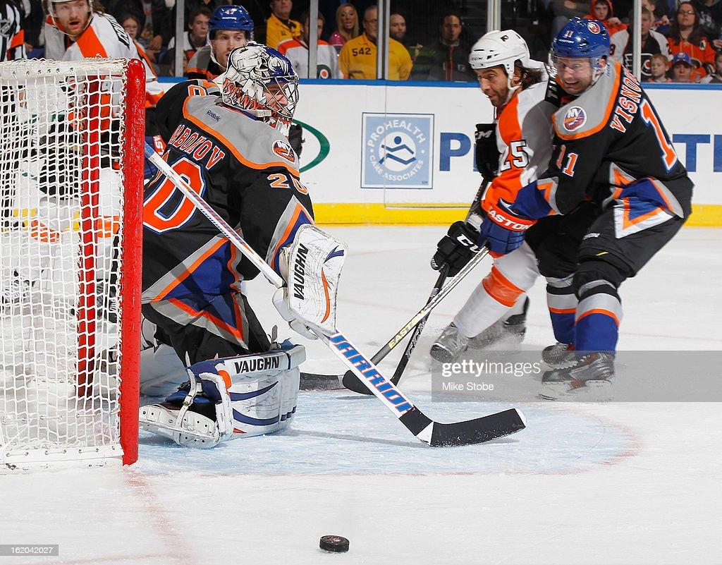 Evgeni Nabokov #20 and Lubomir Visnovsky #11 of the New York Islanders defend the net against Maxime Talbot #25 of the Philadelphia Flyers at Nassau Veterans Memorial Coliseum on February 18, 2013 in Uniondale, New York.