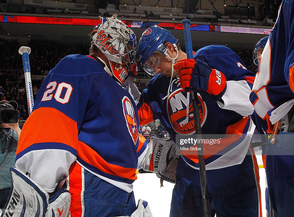 Evgeni Nabokov #20 of the New York Islanders and Travis Hamonic #3 celebrate after defeating the Florida Panthers at Nassau Veterans Memorial Coliseum on April 16, 2013 in Uniondale, New York.