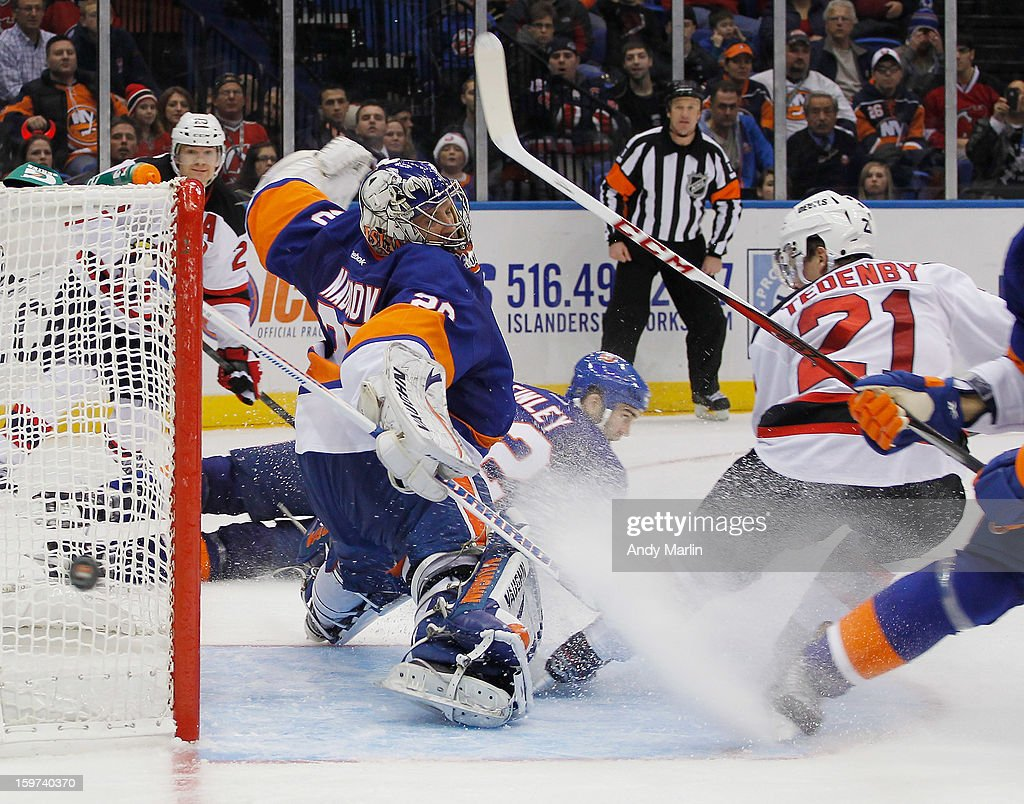 Evgeni Nabokov #20 of the New York Islanders deflects the puck behind the net on a close in shot by Mattias Tedenby #21 of the New Jersey Devils during the Islanders home opener at the Nassau Coliseum on January 19, 2013 in Uniondale, New York. The Devils defeated the Islanders 2-1.