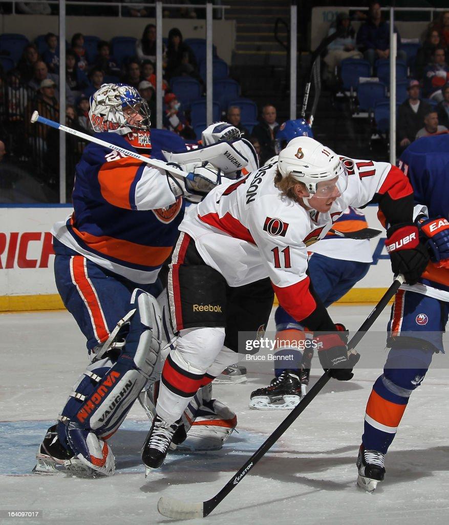 Evgeni Nabokov of the New York Islanders hits Daniel Alfredsson of the Ottawa Senators during thefirst period at the Nassau Veterans Memorial...