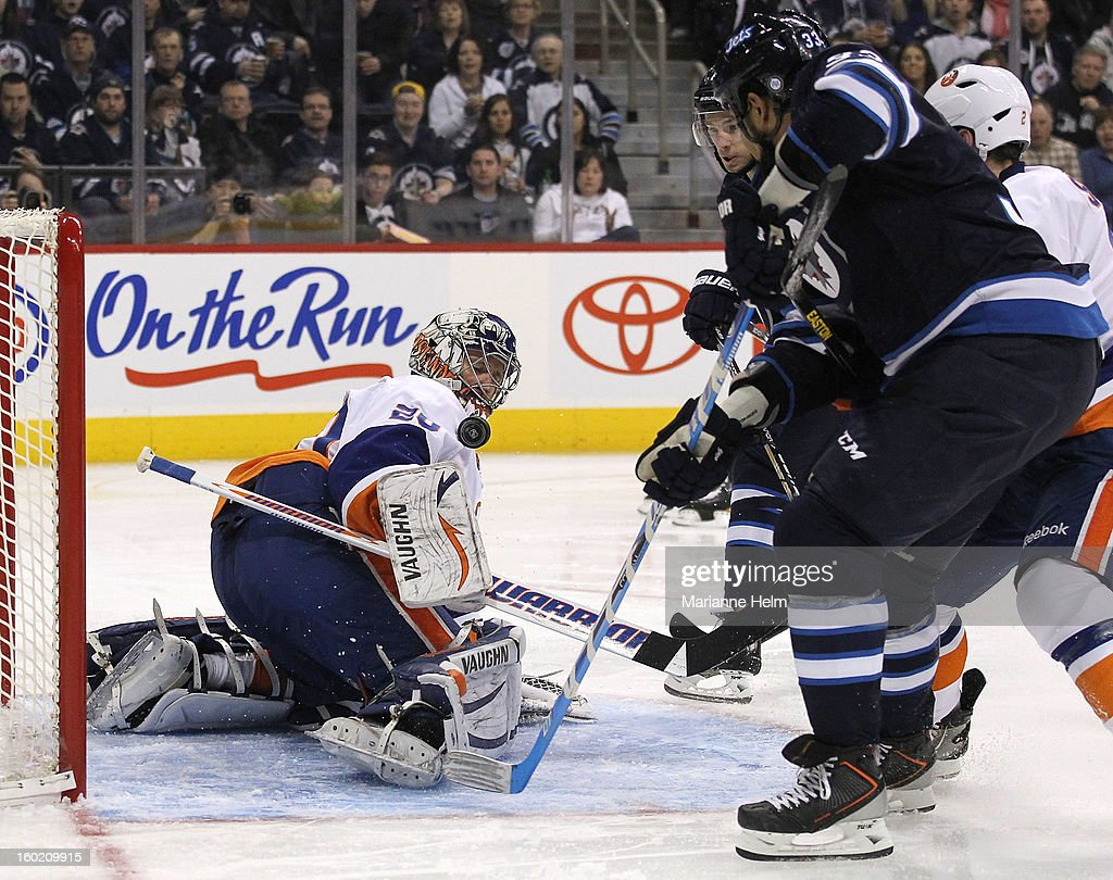Evgeni Nabokov #20 of the New York Islanders keeps his eye on the puck as Dustin Byfuglien #33 of the Winnipeg Jets makes a run for the net in second period action on January 27, 2013 at the MTS Centre in Winnipeg, Manitoba, Canada.