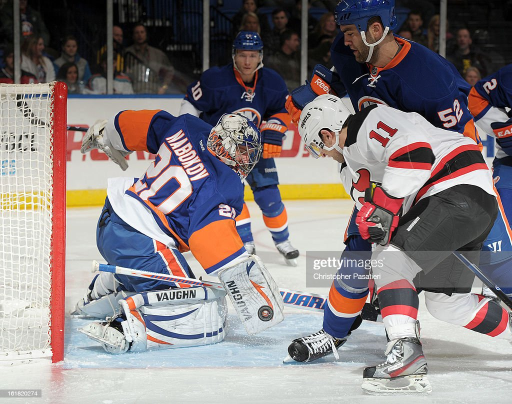 Evgeni Nabokov #20 of the New York Islanders makes a save during the game against the Stephen Gionta #11 of the New Jersey Devils on February 16, 2013 at Nassau Veterans Memorial Coliseum in Uniondale, New York.