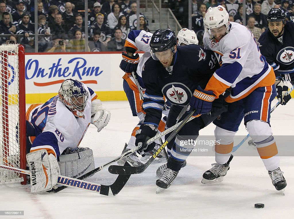 Evgeni Nabokov #20 of the New York Islanders protects his net as Blake Wheeler #26 of the Winnipeg Jets and Frans Nielsen #51 fight for the puck in second period action on January 27, 2013 at the MTS Centre in Winnipeg, Manitoba, Canada.