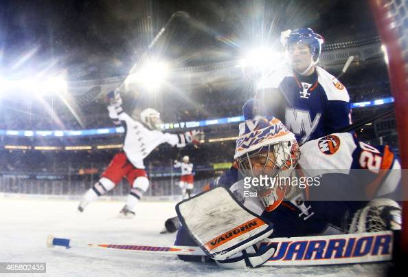 Evgeni Nabokov of the New York Islanders reacts after Benoit Pouliot of the New York Rangers scored a goal in the second period during the 2014 Coors...