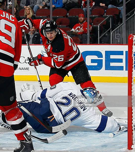 Evgeni Nabokov of the Tampa Bay Lightning make sthe save on Patrik Elias of the New Jersey Devils at the Prudential Center on December 19 2014 in...