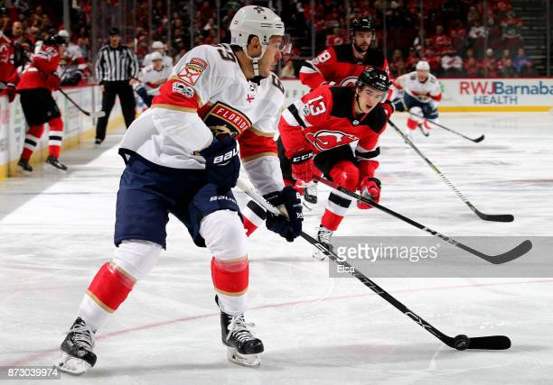 Evgenii Dadonov of the Florida Panthers heads for the net as Nico Hischier of the New Jersey Devils defends on November 11 2017 at Prudential Center...