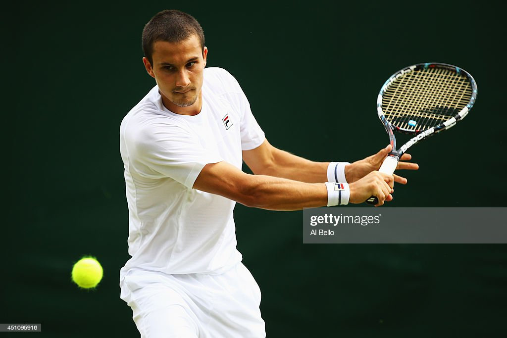 <a gi-track='captionPersonalityLinkClicked' href=/galleries/search?phrase=Evgeny+Donskoy&family=editorial&specificpeople=5368047 ng-click='$event.stopPropagation()'>Evgeny Donskoy</a> of Russia plays a backhand during his Gentlemen's Singles first round match against Bernard Tomic of Australia on day one of the Wimbledon Lawn Tennis Championships at the All England Lawn Tennis and Croquet Club at Wimbledon on June 23, 2014 in London, England.
