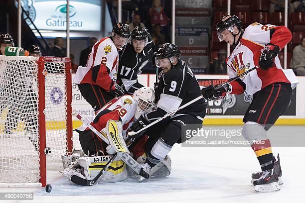 Evgeny Kiselev of the Baie Comeau Drakkar makes a save as Yan Aucoin and Nicolas Meloche defends against Yan Pavel Laplante and Joey Richard of the...