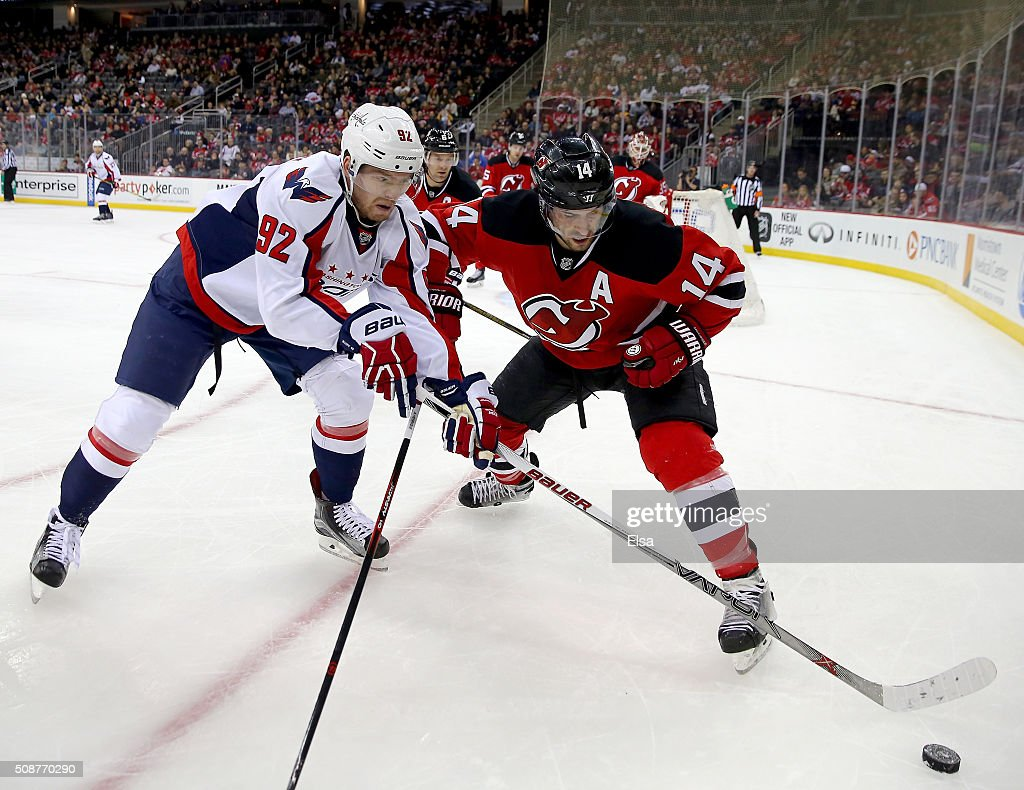 Evgeny Kuznetsov #92 of the Washington Capitals and <a gi-track='captionPersonalityLinkClicked' href=/galleries/search?phrase=Adam+Henrique&family=editorial&specificpeople=4043225 ng-click='$event.stopPropagation()'>Adam Henrique</a> #14 of the New Jersey Devils fight for the puck in the first period on February 6, 2016 at Prudential Center in Newark, New Jersey.